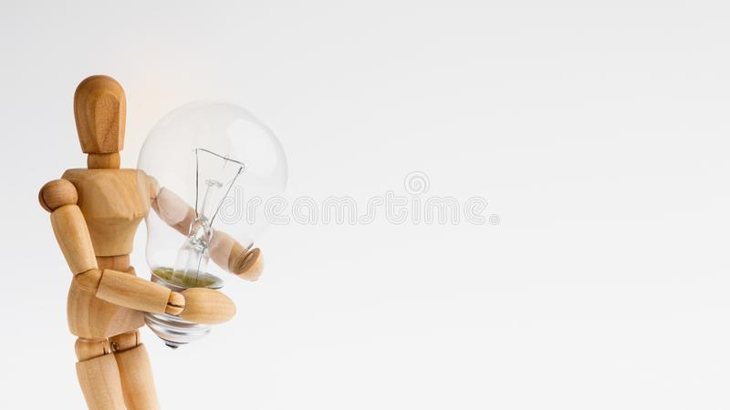 Wooden mannequin figure holding lamp bulb on white royalty free stock photography