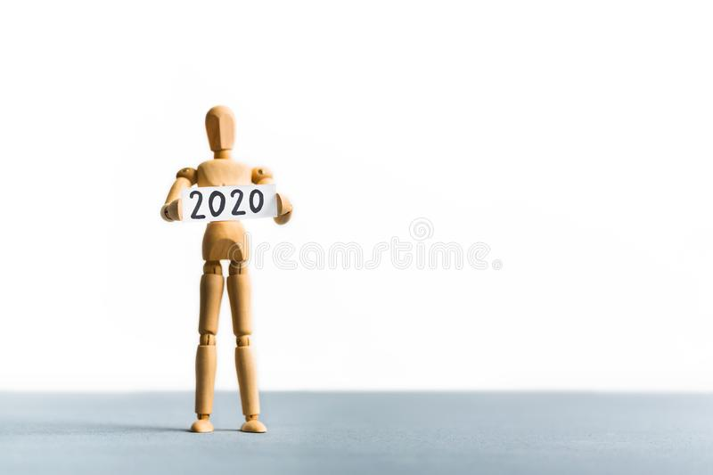 Wooden mannequin holding 2020 year sign in hands stock photos