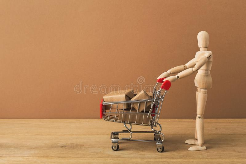 Wooden mannequin with miniature shopping cart stock images