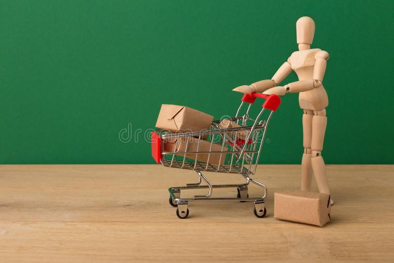 Wooden mannequin with miniature shopping cart royalty free stock photos