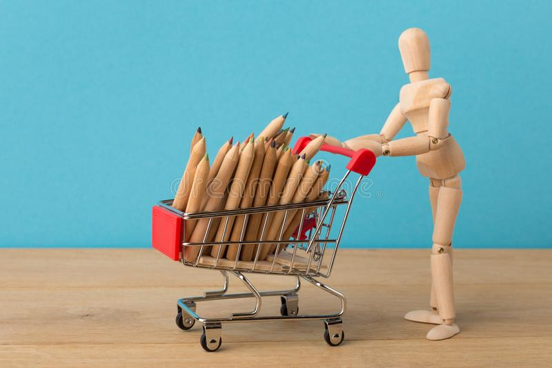 Wooden mannequin with miniature shopping cart stock photo