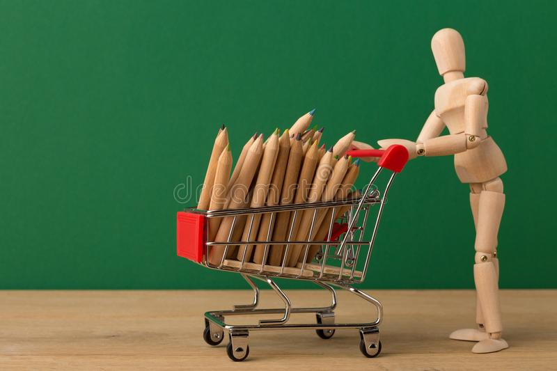 Wooden mannequin with miniature shopping cart stock photography