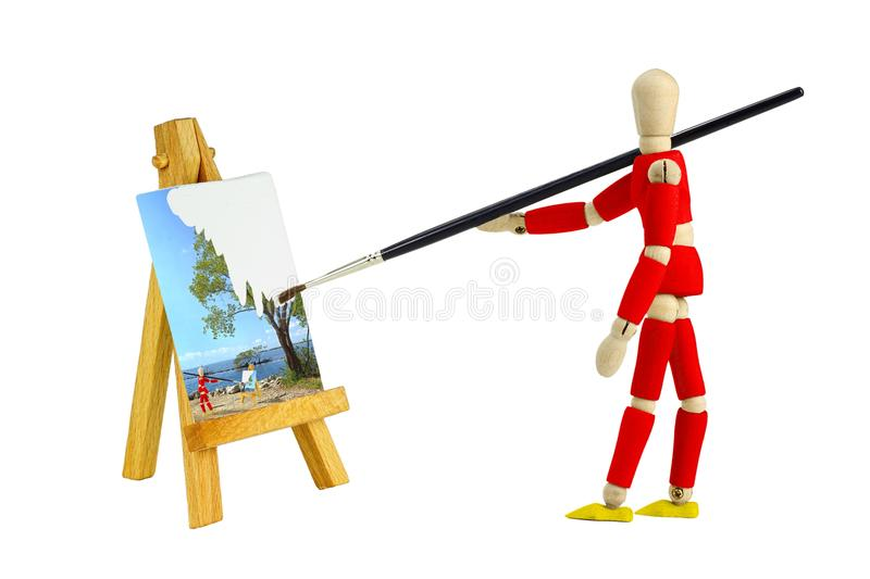 Wooden mannequin painting a landscape isolated on stock photo