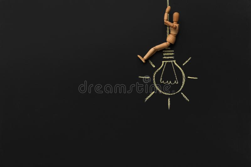 Wooden mannequin sitting on drawn electric bulb stock image