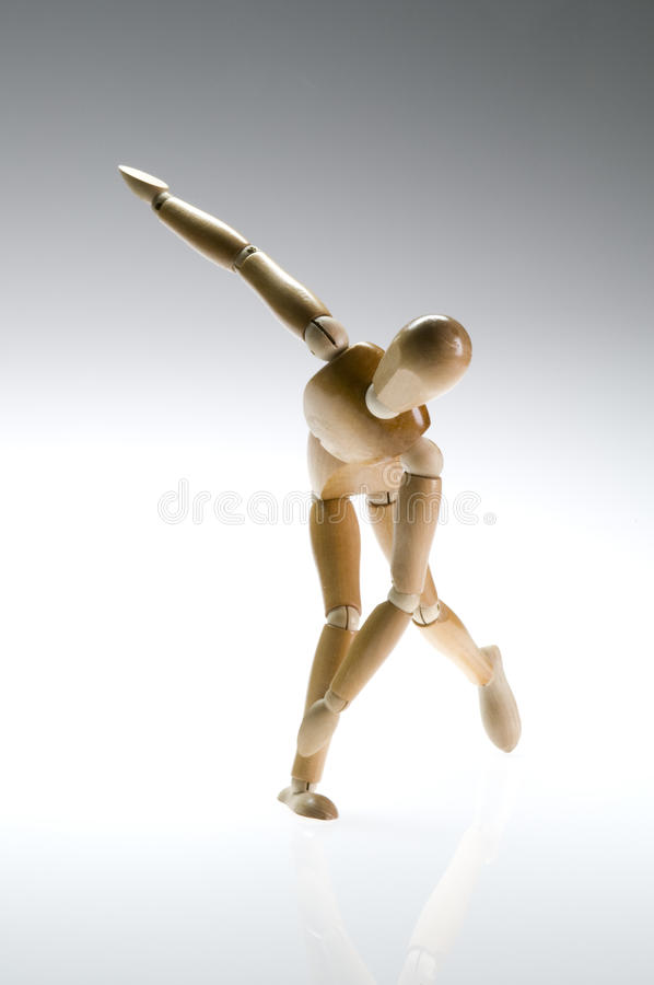Wooden Mannequin Twist. Wooden artist mannequin posed as a speed skater or a discus thrower royalty free stock photo
