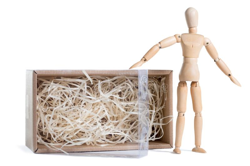 Wooden mannikin standing near open cardboard box filled with wood shred. Concept of thinking outside the box, freedom. stock photography