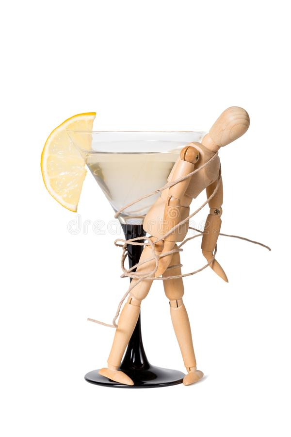 Wooden mannikin strapped to the glass of vermouth. Concept of drunkenness, alcohol abuse royalty free stock image