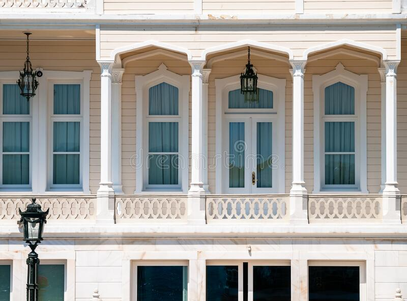 Wooden mansion close up detail. Beautiful classic architecture balcony with arch  columns and many windows stock images
