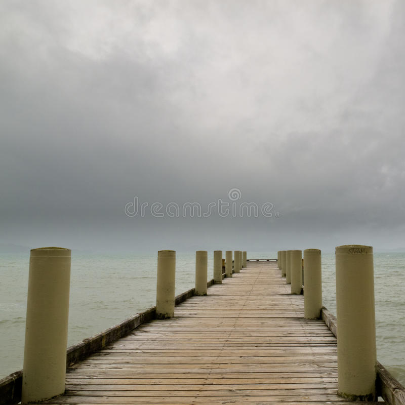 Wooden marine pier on an overcast day royalty free stock photo