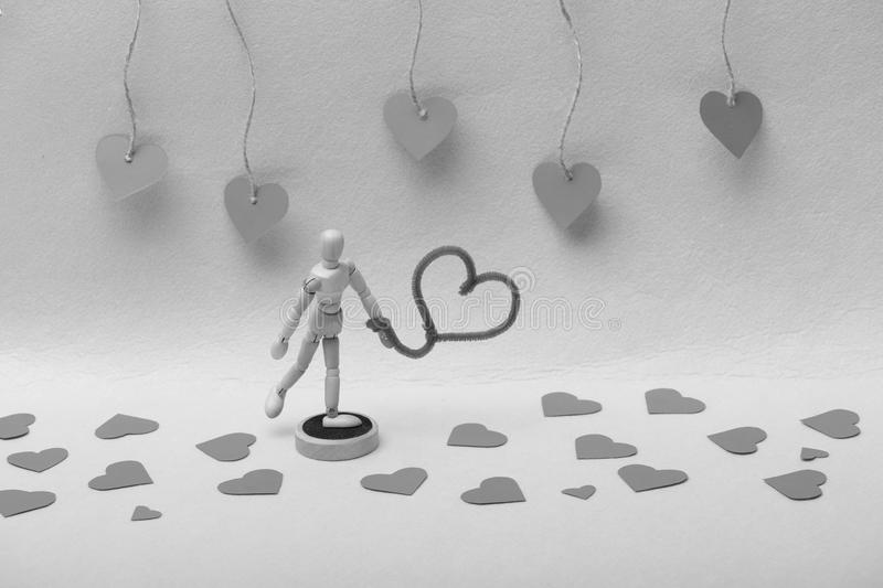 Wooden marionette standing with fuzzy wire heart stock photo