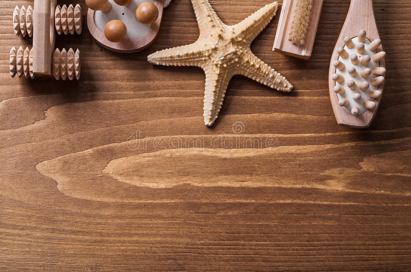 Wooden massagers starfish and nailbrush on pine. Vintage board sauna concept stock photography