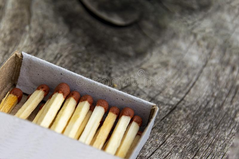 Wooden match in box on a wooden background. Fire safety concept, fire and tree. Close-up shot. Matches in an open matchbox on a stock photography