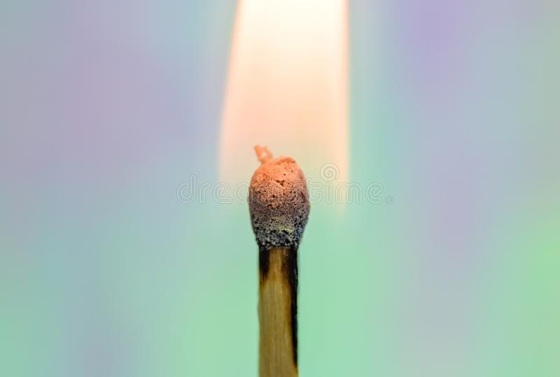 Burning Match with Rainbow Background. A wooden match flame burns brightly against a soft, colorful rainbow holographic background royalty free stock images
