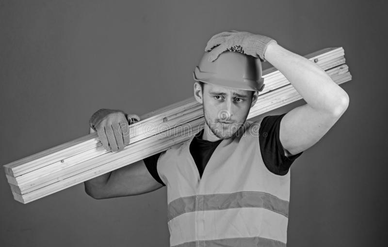 Wooden materials concept. Man in helmet, hard hat and protective gloves holds wooden beam, grey background. Carpenter stock image