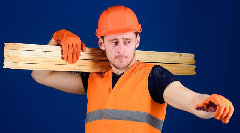 Wooden materials concept. Man in helmet, hard hat and protective gloves pointing direction, blue background. Carpenter. Woodworker, strong builder on busy face royalty free stock photo