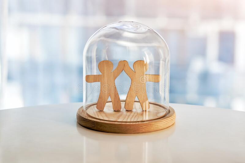 Wooden men under glass cap royalty free stock photos
