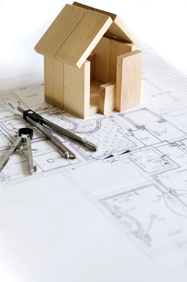Wooden model of house and blueprints stock photos