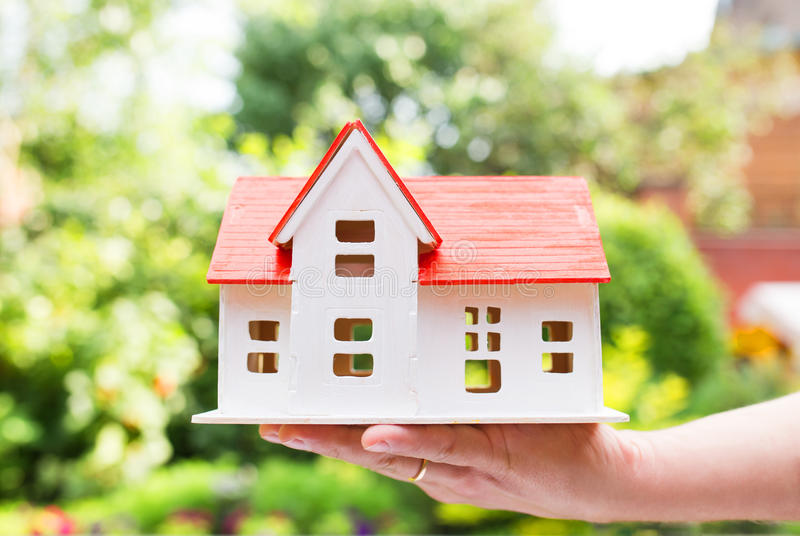 Wooden model of house in hands stock images