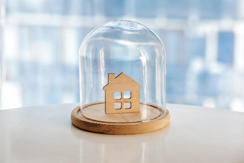 Wooden model of house under glass cap stock image