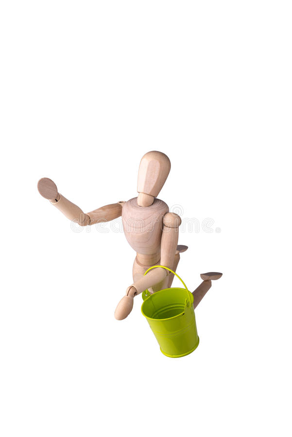 Wooden model of human. Wooden model of the person with a bucket in hands on the white isolated background stock image
