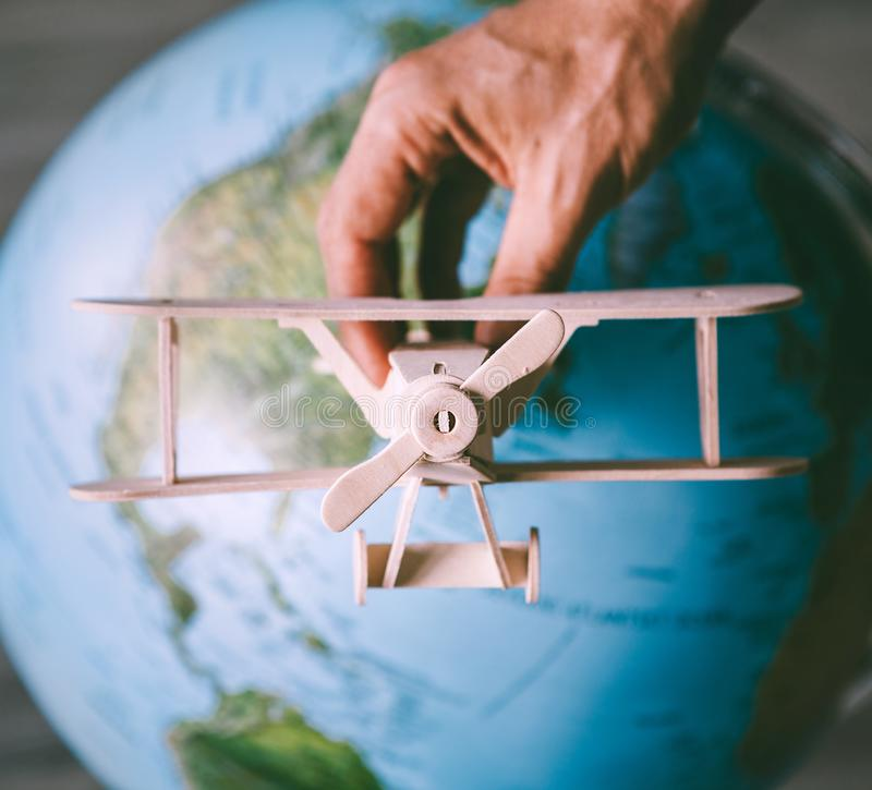 Wooden model vintage airplane fly near the Earth globe royalty free stock photo