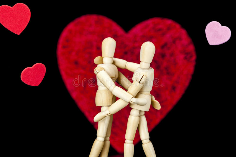 Wooden models. Embrace with hearts stock image