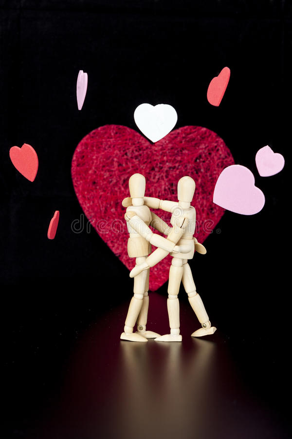 Wooden models. Embrace, with hearts stock image