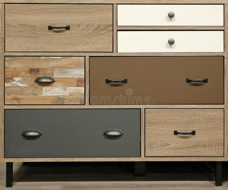 Wooden modern chest of drawers with drawers of different shapes and colors.  stock photos