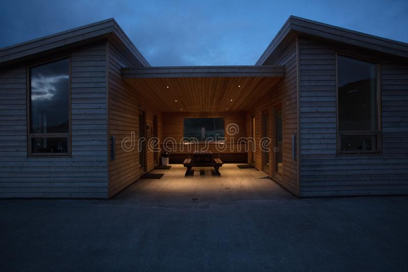 A wooden modern house with benches in the middle stock photography