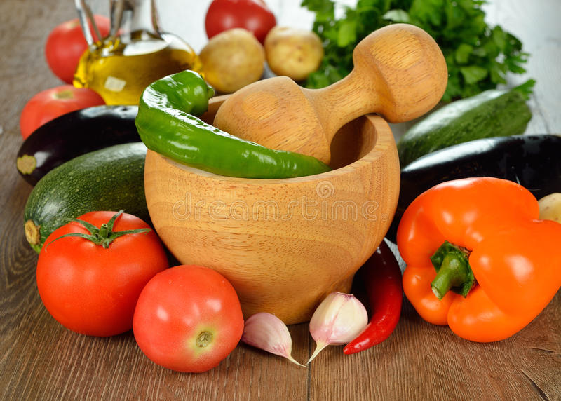 Wooden mortar and fresh vegetables stock image