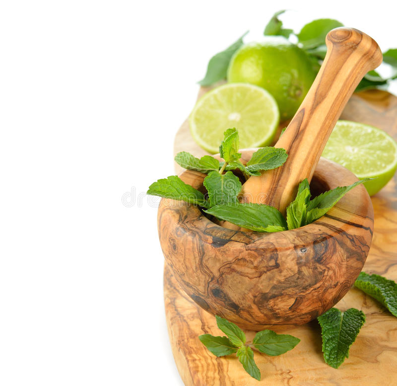 Wooden mortar, mint and limes stock photos