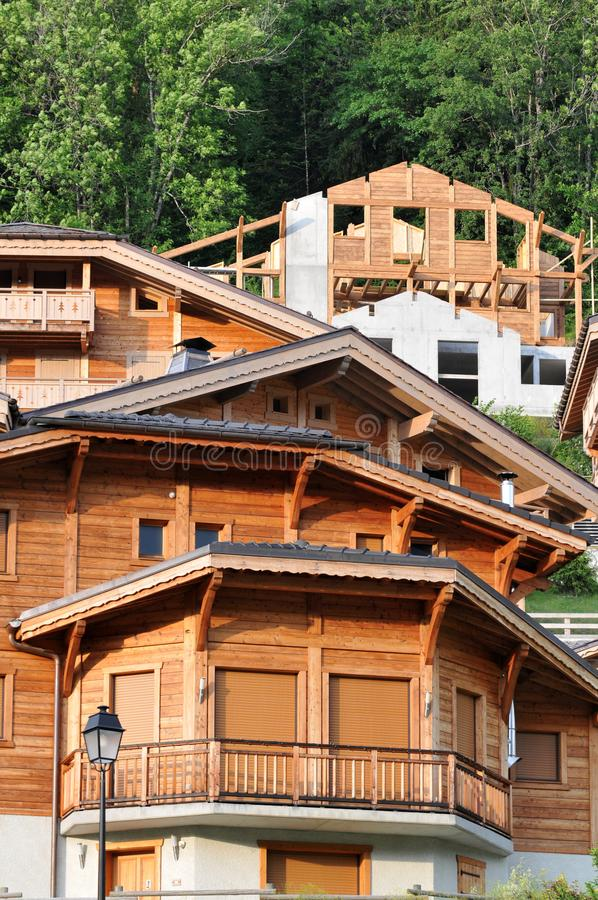 Mountain chalets in the French Alps. Wooden mountain houses including one under construction stock photo