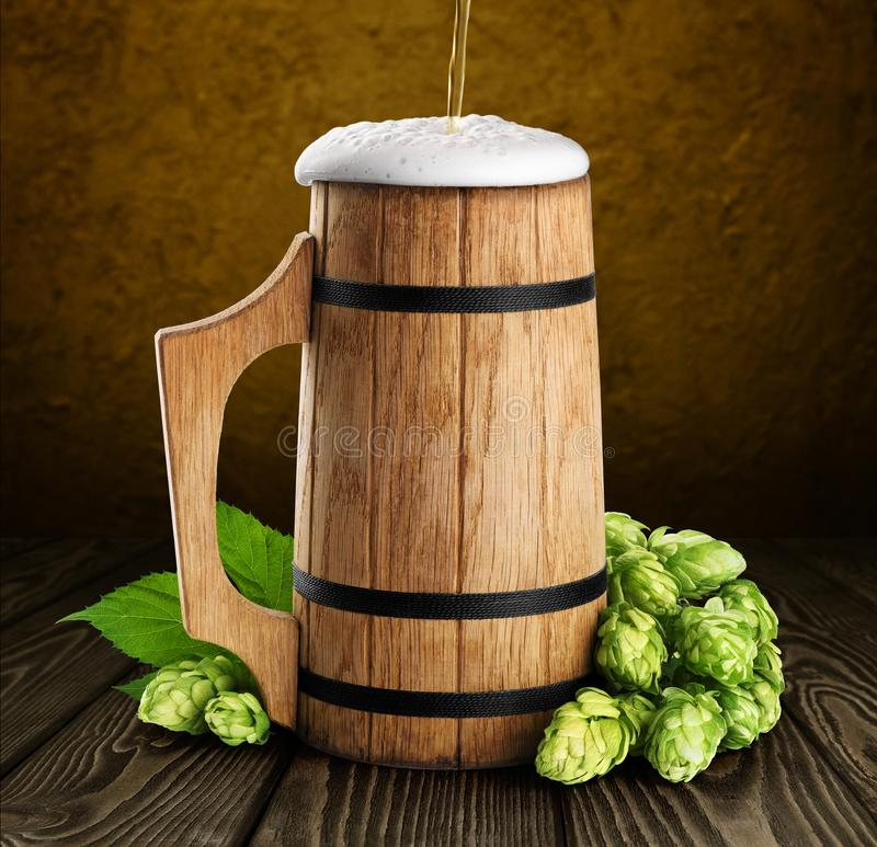 Wooden mug with beer and hops. On a dark background royalty free stock photography
