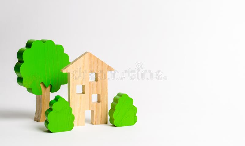 Wooden multi-storey building surrounded by bushes and trees. Urbanism and urban landscaping. Acquisition of affordable housing in stock images
