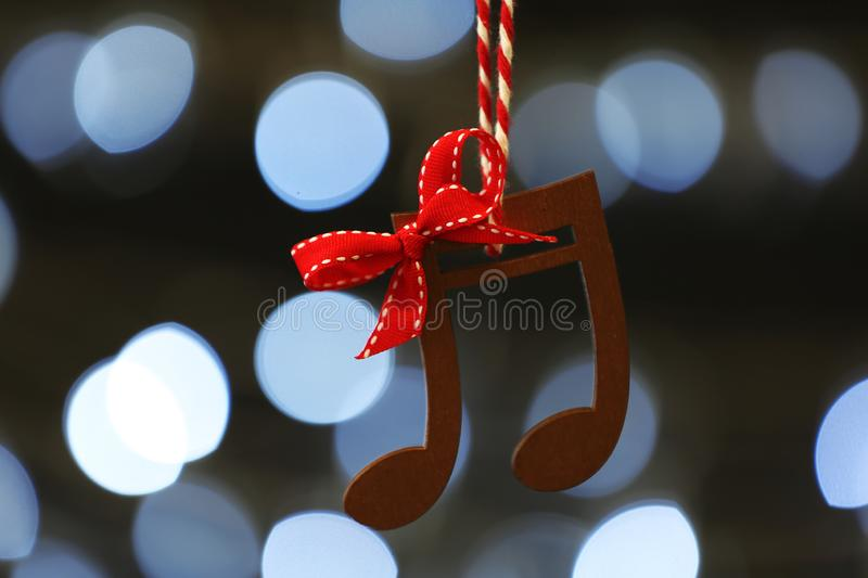 Wooden music notes against Christmas lights. Wooden music notes against blurred Christmas lights stock images