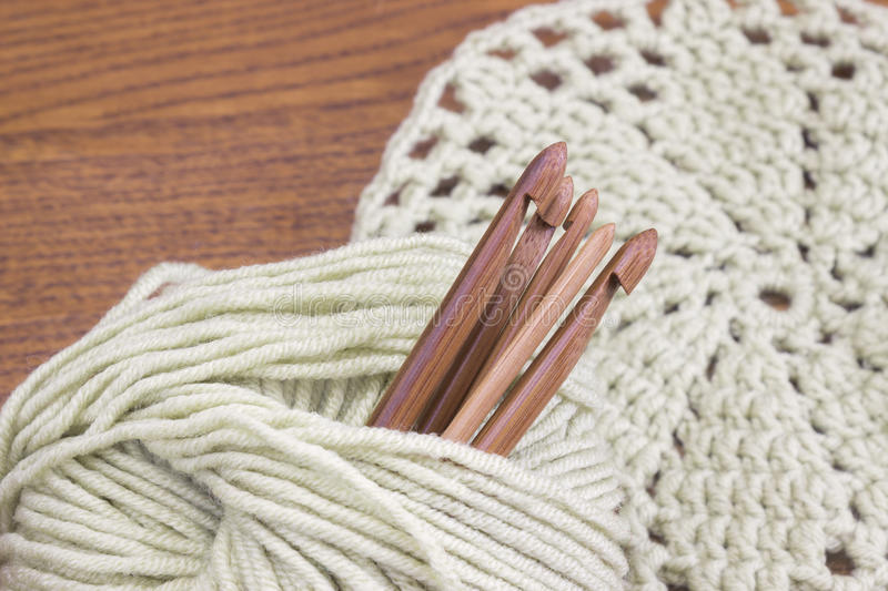 Wooden natural bamboo crochet hooks, doily and yarn ball on the table. Creative work place for homemade crafts. Top view. stock photo