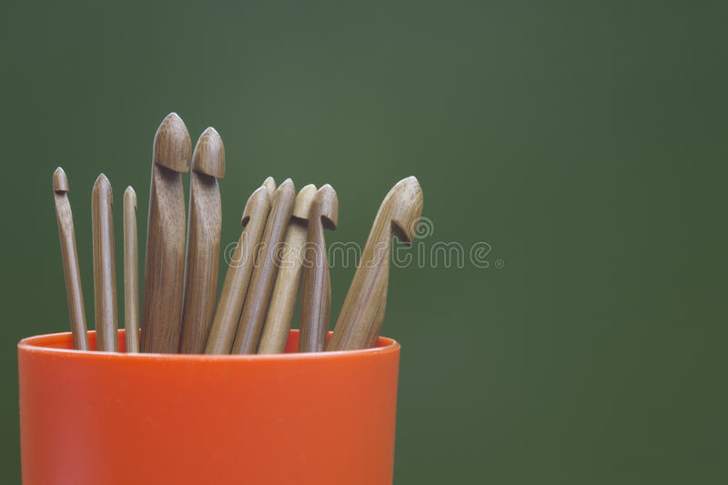 Wooden natural bamboo crochet hooks in the plastic container. Various sizes. Creative work place for homemade crafts. Wooden natural bamboo crochet hooks in the stock images