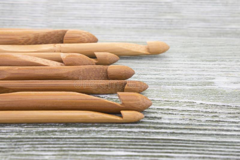 Wooden natural bamboo crochet hooks on the table. Various sizes. Creative work place for homemade crafts. Top view. Wooden natural bamboo crochet hooks on the stock photo