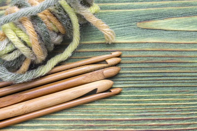 Wooden natural bamboo crochet hooks and yarn ball on the green table. Creative work place for homemade crafts. Top view, place for. Text, copyspace stock photography