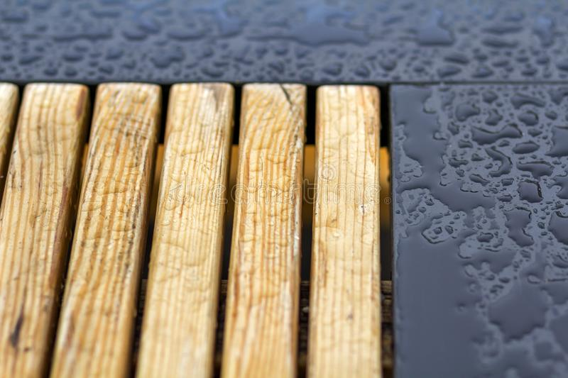 Wooden natural planks, polished boards, garden park bench with transparent big clear rain water drops on blue gray wet background stock photography