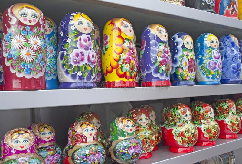 Wooden nesting dolls of different colors are on the sales counter. Wooden nesting dolls are sold as souvenirs stock images
