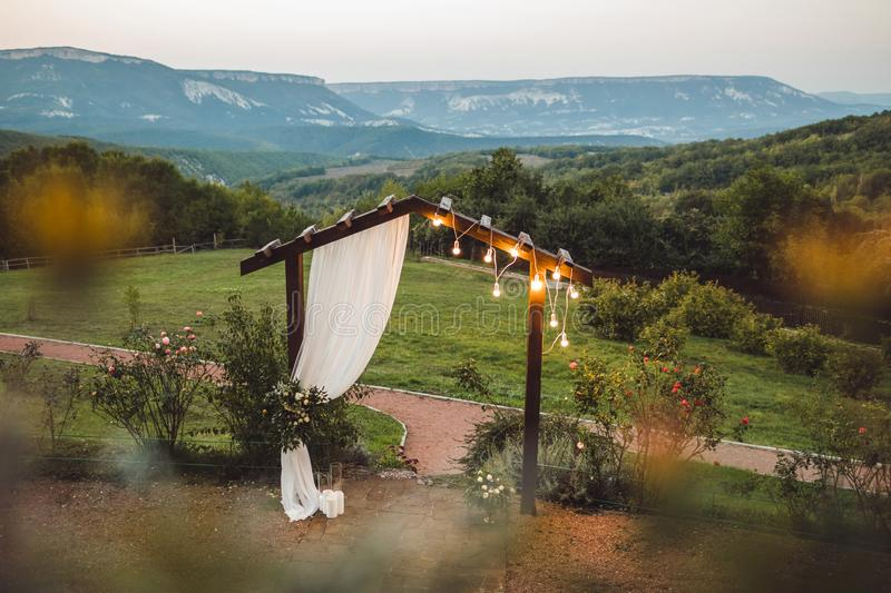 Wooden night wedding arch with light bulbs outdoor royalty free stock photo