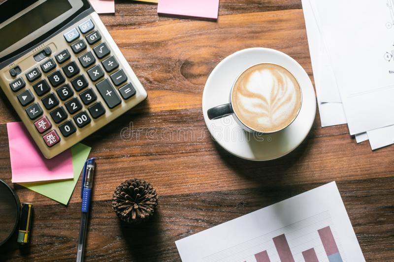 Wooden office desk with cup coffee calculator and chart graph document, copy space for your text.Top view stock photography