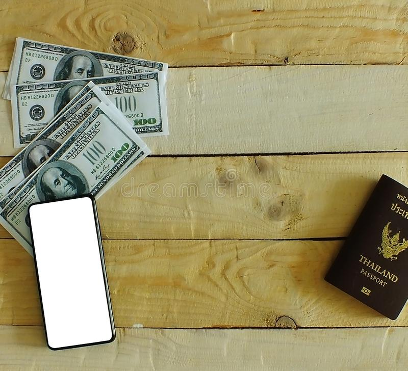 The wooden office desk has bank notes, mobile phones and passports on the desk. Prepare to travel stock image