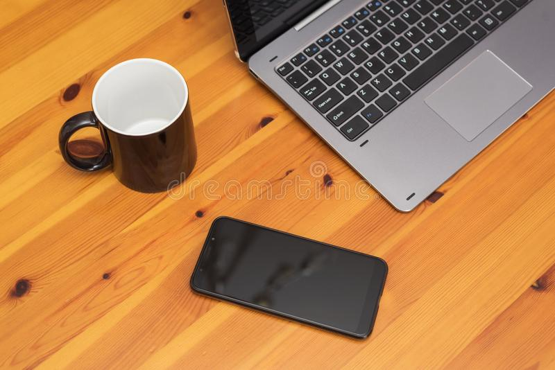 Wooden office desk table with laptop, cup and smartphone. stock images