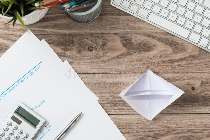 Wooden office desk with white origami boat. Professional invest management and consulting. Flat lay office workplace with business reports, computer keyboard royalty free stock photography
