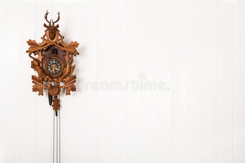 Wooden old cuckoo clock hanging on a white wall. royalty free stock photography