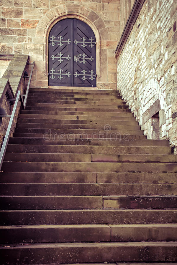 Wooden old door and steps. Wooden old door with wrought-iron elements and steps royalty free stock photo