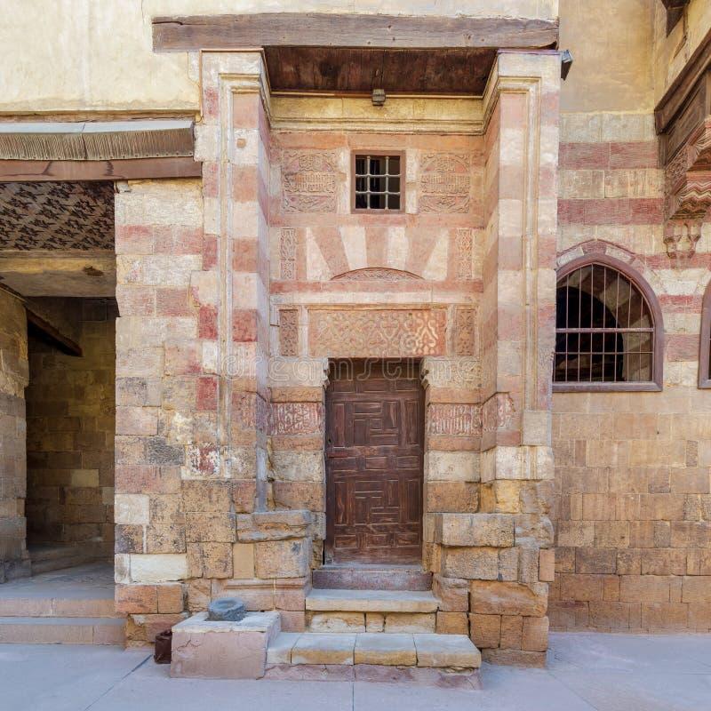 Wooden old grunge decorated door at courtyard of El Razzaz Mamluk era historic house, Darb Al-Ahmar district, Old Cairo, Egypt. Wooden old grunge decorated door stock photos