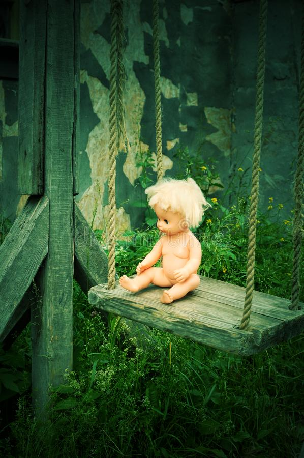 Wooden old a swing with a plastic doll stock photography